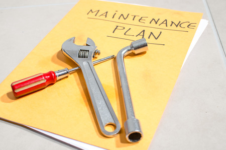 Verschillende instrumenten op een map van onderhoudsplan Stockfoto