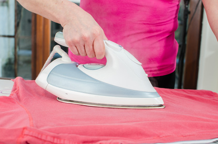 woman ironing: Woman ironing a red tee shirt