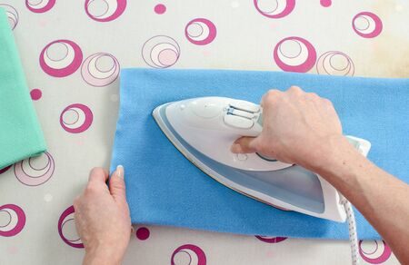 the iron lady: Woman ironing a blue dishcloth, top view