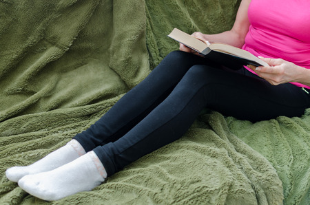 green couch: Woman reading a book on a green couch