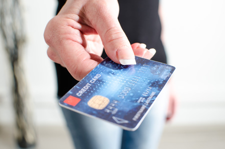 pagando: Mano de la mujer que muestra la tarjeta de crédito, de cerca Foto de archivo