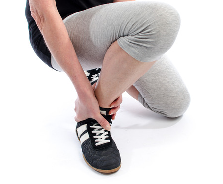 Woman holding her sore ankle photo