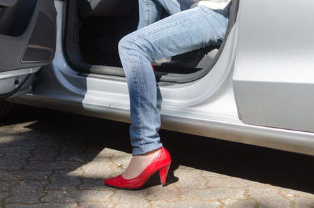 Leg of woman going out of a car