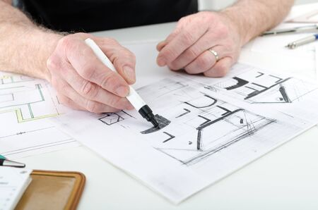architect: Architect working on plans of  new house Stock Photo