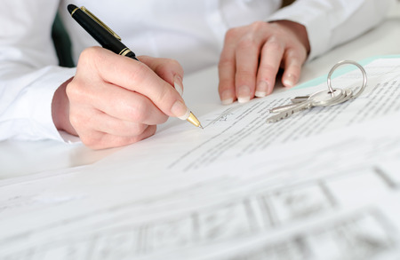agente comercial: Cliente de firmar un contrato de bienes raíces en la agencia de bienes raíces Foto de archivo