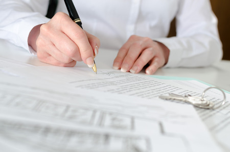 real estate contract: Client signing a real estate contract in real estate agency