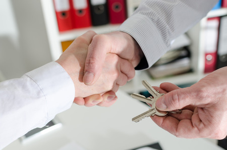 shaking hands with his client by delivering the keys, closeup