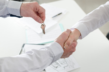 shaking hands with his client by delivering the keys Stok Fotoğraf