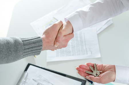 handing over: shaking hands with his client after handing over the keys