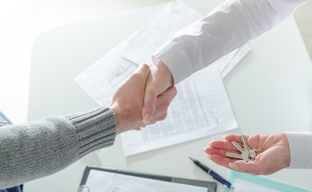 Realtor shaking hands with his client after handing over the keys Foto de archivo