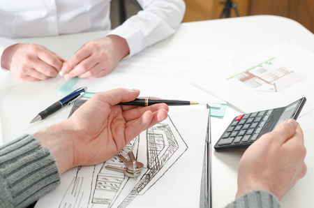 home prices: showing the home prices on a calculator to his client in real estate agency Stock Photo