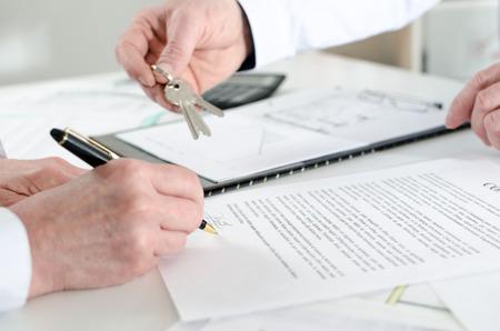 contratos: Cliente de firmar un contrato de bienes raíces en la agencia de bienes raíces Foto de archivo