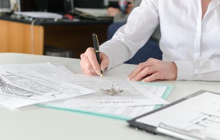Client ondertekenen van een onroerend goed contract in makelaardijen Stockfoto