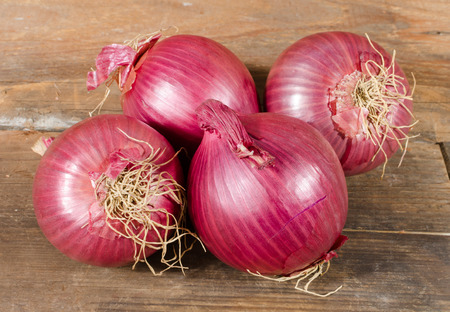 Fresh bulbs of red onions on wooden background