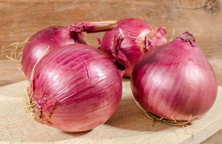 flavorings: Fresh bulbs of red onions on wooden background Stock Photo
