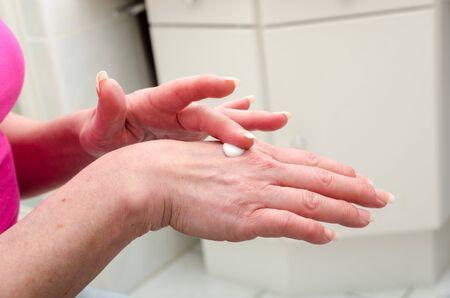 moisturizers: Woman applying cream on her hand in the bathroom