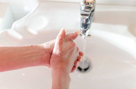 rinsing: Woman rinsing her hands in sink with water Stock Photo