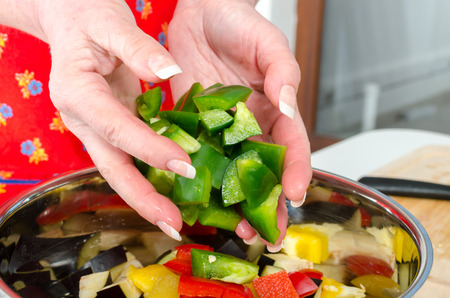 adding: Hand of woman adding pieces of green pepper into saucepan