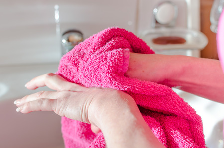 hand towel: Woman drying her hands with a pink towel