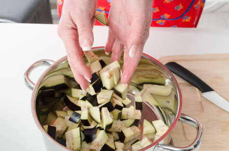 Hand of woman adding pieces of eggplant into saucepan photo