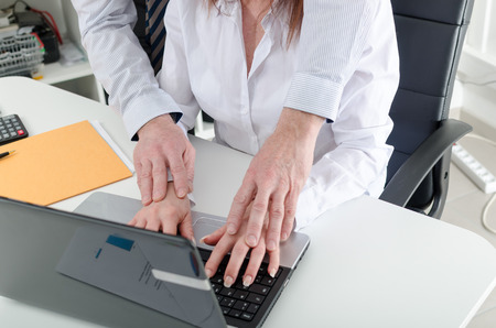 harassment: Manager putting his hands on the hands of his secretary, at office Stock Photo