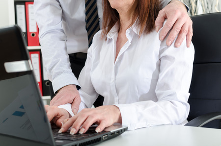 woman boss: Manager putting his hand on the shoulder of his secretary, at the office