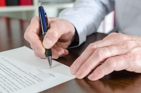 Businessman signing a document, closeup