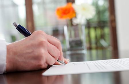 Businesswoman signing a document, closeup Foto de archivo