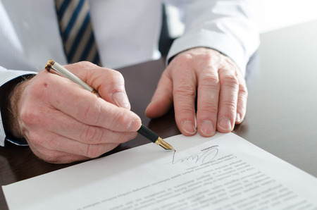 business letters: Businessman signing a document, closeup