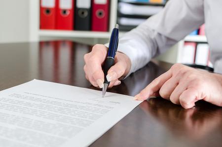 Onderneemster die een document op kantoor ondertekent