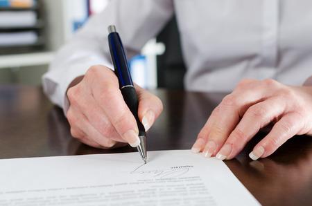 Zakenvrouw ondertekening van een document op het kantoor Stockfoto