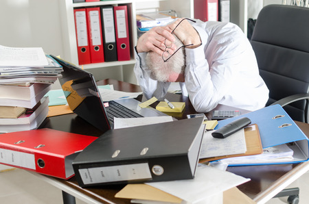 Stressed businessman holding his head in his hands Stock Photo