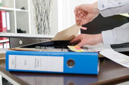 messy desk: El hombre de negocios en busca de su tel�fono en su escritorio desordenado