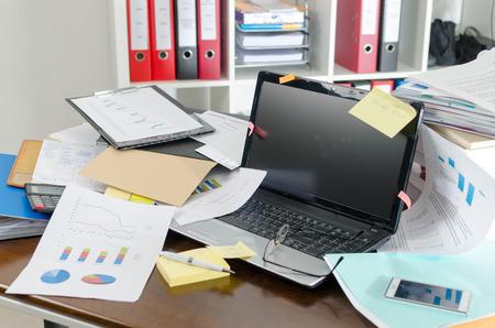 oficina desordenada: Vista de un escritorio desordenado y desordenado Foto de archivo
