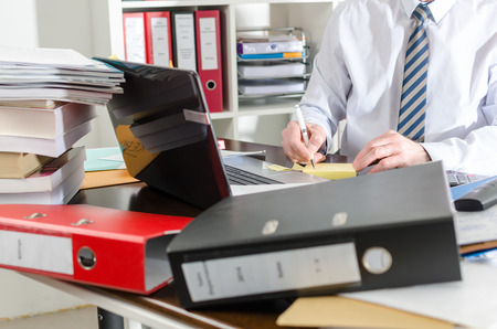 untidy: Businessman working at a untidy and cluttered desk