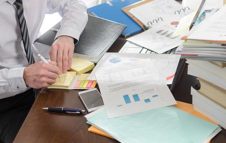oficina desordenada: Hombre de negocios trabajando en un escritorio desordenado y desordenado Foto de archivo