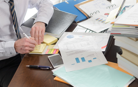 Zakenman werken op een slordig en rommelig bureau
