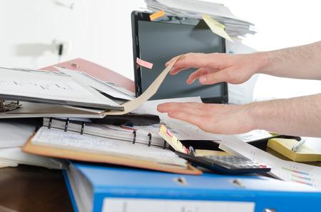 suo: Uomo d'affari alla ricerca di suo telefono sulla sua scrivania disordinata