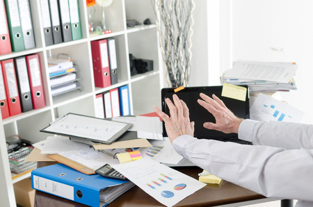 Businessman refusing to see his cluttered desk Foto de archivo