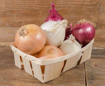cebolla: Los diferentes tipos de cebollas en una cesta en el fondo de madera