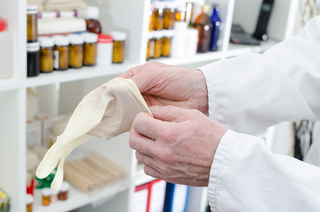 latex glove: Doctor putting on a latex glove in medical office