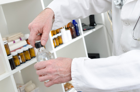 antiseptic: Doctor opening a bottle of antiseptic in medical office Stock Photo