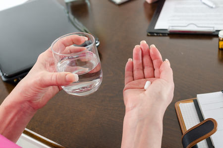 take medicine: Patient taking her medicine with a glas of water
