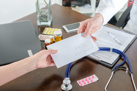 medical physician: Doctor giving a prescription to his patient in medical office