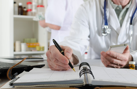 medical notes: Doctor holding a smartphone and taking notes in medical office