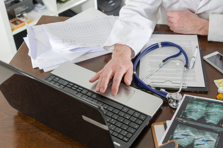 prescribing: Doctor using a laptop at his desk Stock Photo