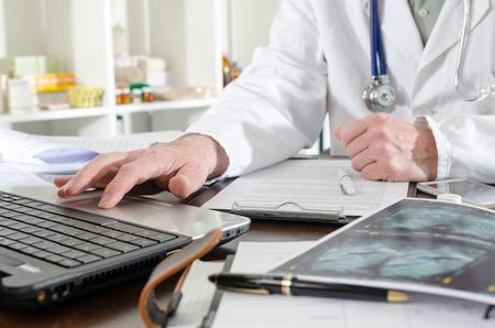 Doctor met behulp van een laptop in de medische kantoor Stockfoto