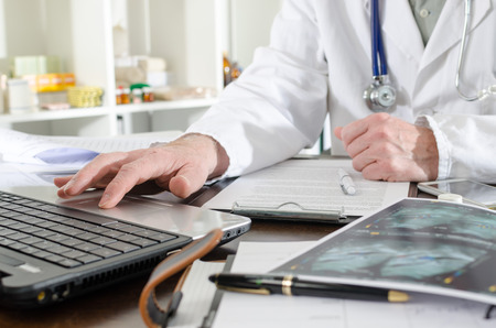 doctores: Doctor que usa un ordenador port�til en la oficina m�dica