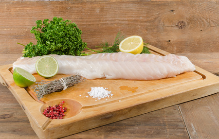 whitefish: Cod fillet on wooden board
