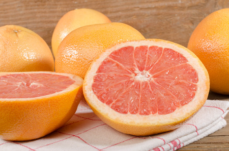 grapefruits: Fresh grapefruits on towel on wooden background